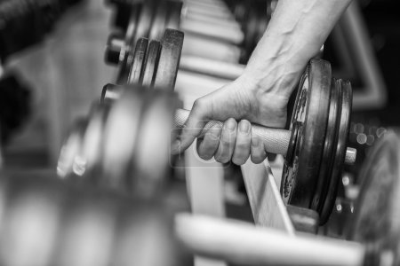 Hand holding a dumbbell in gym
