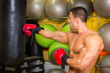 Muscular man in boxing gloves in gym