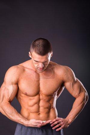 Man holding a pill, amino acids