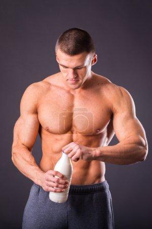 Bodybuilder holding a bottle of milk