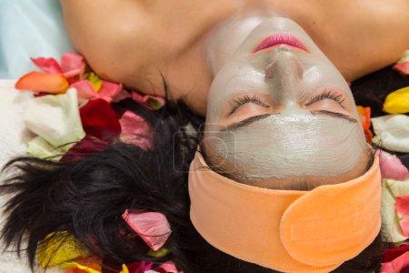 Woman with facial mask at beauty salon