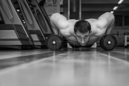 Man doing push up exercise with dumbbells