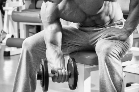 Muscular man working out with dumbbells