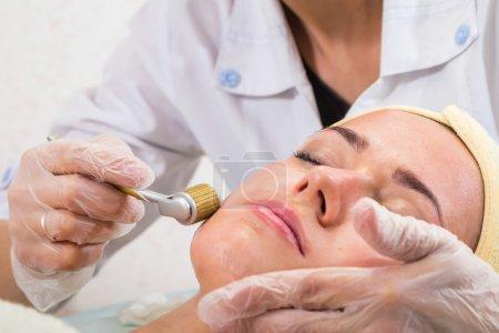 Photo pour Soins de beauté dans le salon de beauté. Éjaculation faciale revitalisant d'esthéticienne. Massage facial. Esthéticienne du visage, beauté,. - image libre de droit