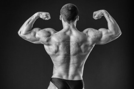 Bodybuilder shows his back muscles.