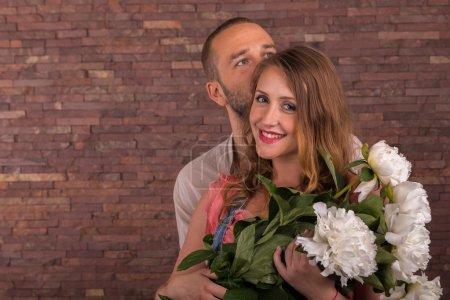 Photo pour Mari et femme avec des fleurs dans le studio. Le thème des relations familiales et l'attente de la naissance du bébé. - image libre de droit