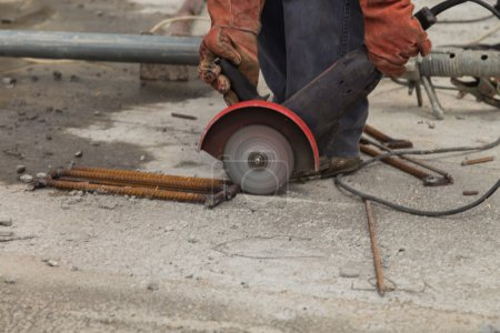 Construction worker cuts metal grinder