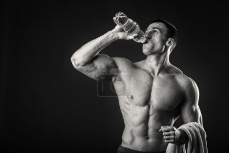 Muscular man on a dark background drinking water after workout