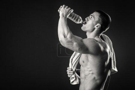 Photo pour Homme musculaire sur un fond sombre boire de l'eau après l'entraînement. Détendez-vous après une séance d'entraînement épuisante. Photos pour magazines sportifs, affiches et sites web - image libre de droit