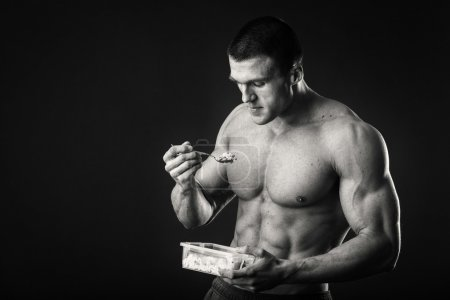 Muscular man eats cottage cheese on a dark background.
