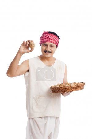 Farmer showing a potato and smiling