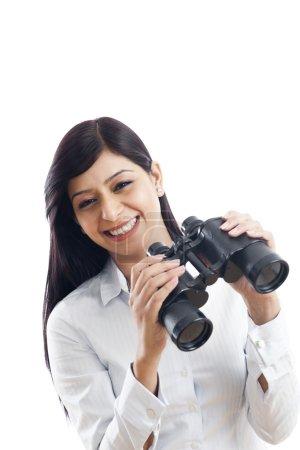 Photo pour Portrait d'une femme d'affaires tenant des jumelles et souriant - image libre de droit
