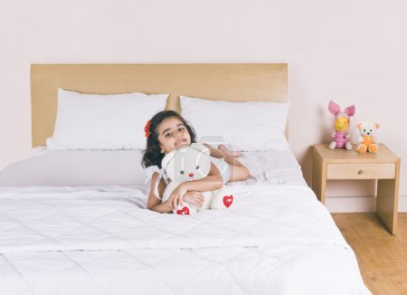 Girl lying on the bed holding a teddy bear and smiling