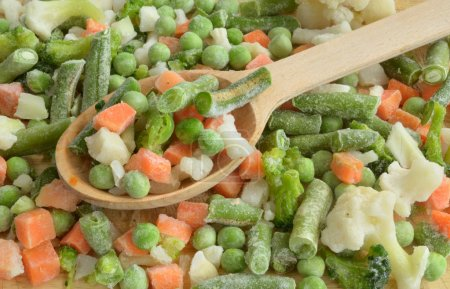 frozen vegetables are in a wooden spoon on the table