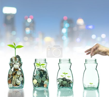 Hand putting mix coins and seed in clear bottle on cityscape photo blurred bokeh background,Business investment growth concept