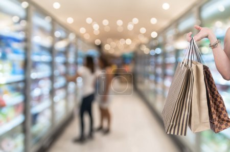 Holding shoping bags by hand on Supermarket blur background with bokeh, Miscellaneous Product shelf