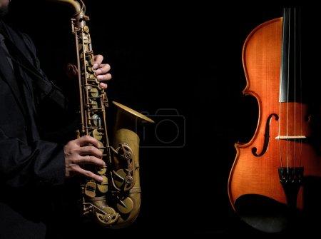 Photo pour Saxophone rapproché en action de joueur avec instruments de musique de l'orchestre de violon sur fond noir - image libre de droit