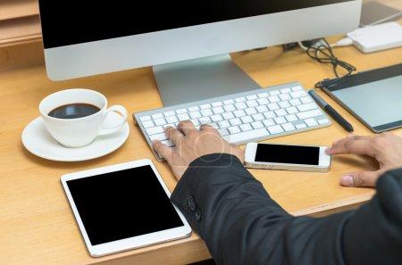 Photo pour Vue d'un homme d'affaires travaillant avec un ordinateur arrière et comprimé au bureau - image libre de droit