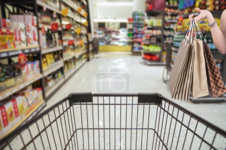 Photo for Holding shoping bags by hand on Supermarket with Abstract blurred photo of store with trolley in department store bokeh background - Royalty Free Image