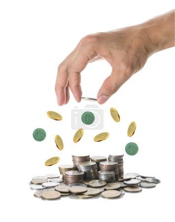 Photo pour Main tenant et ajoutant une pièce sur les piles de pièces mélangées sur fond blanc, Concept de croissance des investissements des entreprises - image libre de droit
