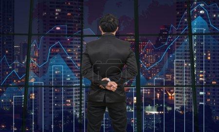 Photo pour Face arrière de Businessman regardant le graphique Trading sur le paysage urbain la nuit et fond de carte du monde, Concept financier d'entreprise - image libre de droit