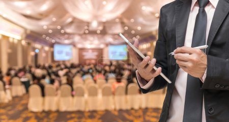 Photo for Businessman using the tablet on the Abstract blurred photo of conference hall or seminar room with attendee background - Royalty Free Image