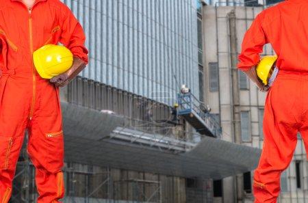 Photo pour Ingénieurs asiatiques tenant un casque jaune sur la photo floue des ouvriers de construction site, concept construction industrielle - image libre de droit