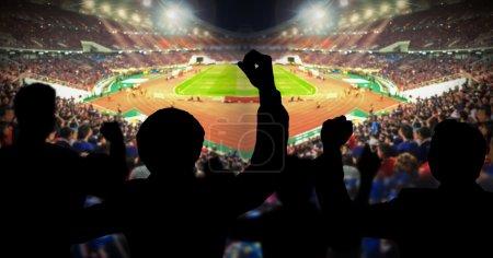 Photo pour Silhouettes de fans de football acclamant contre le grand stade avec lumières, concept sportif - image libre de droit