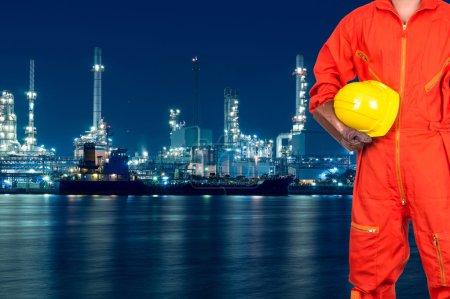 Photo pour Ingénieur asiatique tenant un casque jaune sur une raffinerie de pétrole et de gaz ou une usine pétrochimique au crépuscule, concept industriel - image libre de droit