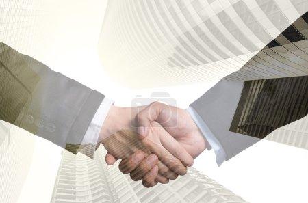 Double exposure handshake between businessmen