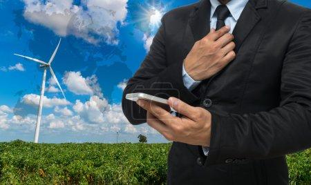 Foto de Empresario usando el teléfono inteligente en el generador de energía de aerogeneradores en el cielo azul, Elementos de esta imagen proporcionados por la NASA . - Imagen libre de derechos