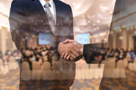 Photo for Double exposure of businessman handshake over the Abstract blurred photo of conference hall or seminar room with attendee background, business agreement concept - Royalty Free Image