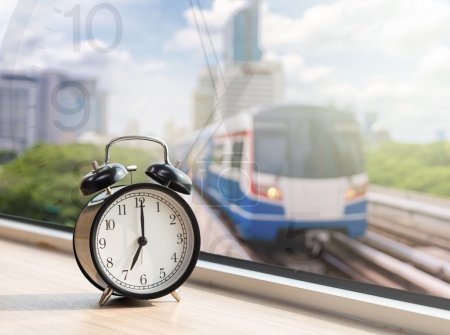 Photo for Vintage alarm clock at window with abstract Blurred photo of sky train with traffic jam on early morning, traffic tranportation concept - Royalty Free Image