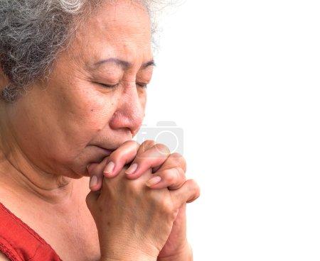 Old woman praying on white background