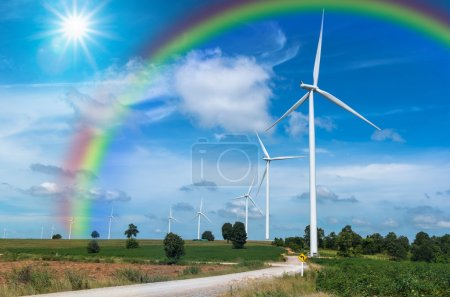 Wind turbine power generator with rainbow on blue sky