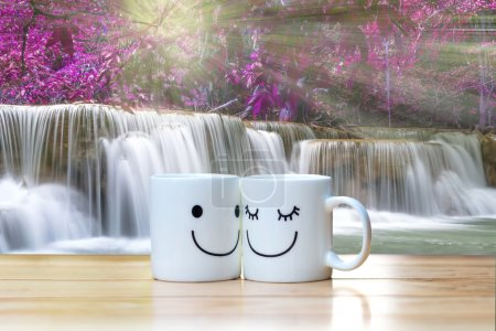 Two happy cups on wood table with Beautiful waterfall in the for