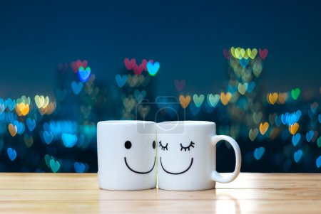 Two happy cups on wood table with heart bokeh background