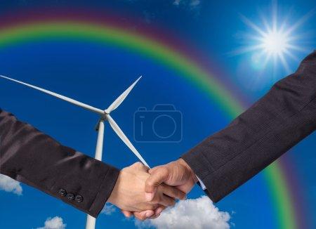 Foto de Agitar la mano entre un hombre de negocios en el fondo del generador de energía de aerogeneradores - Imagen libre de derechos