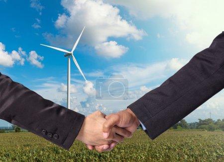 Photo pour Serrer la main entre un homme d'affaires sur fond de générateur d'énergie éolienne - image libre de droit
