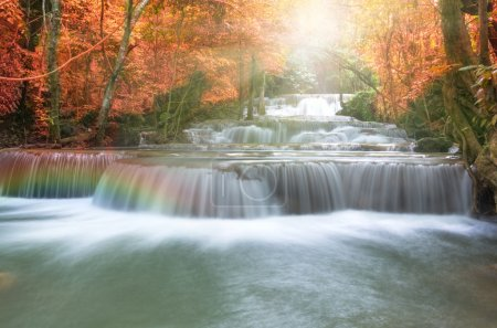 Beautiful waterfall in soft focus with rainbow in the forest