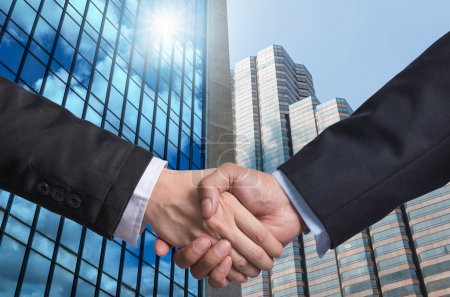 Hand shake between a businessman on Modern glass building background