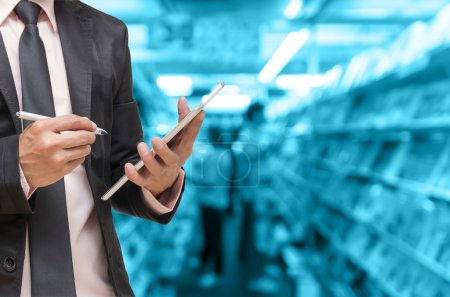 Businessman using the tablet on Abstract blurred photo of book store background, blur color tone