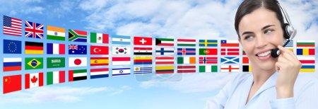 Photo pour Contactez-nous, opérateur de service à la clientèle femme avec casque souriant isolé sur les drapeaux internationaux et le fond du ciel - image libre de droit