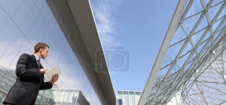 Photo for Businessman with tablet that looks far into the sky, in a scene of urban building with many glass windows - Royalty Free Image