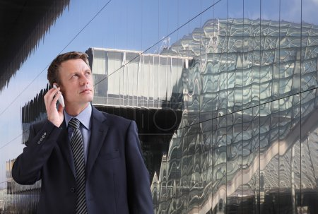 Photo for Business man talking on the phone looking up through the glass buildings - Royalty Free Image