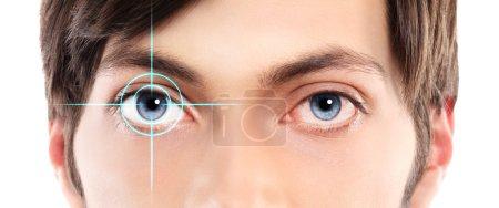 Photo pour Gros plan des yeux bleus d'un œil rouge et irritée de jeune homme avec hologramme laser sur son oeil - image libre de droit