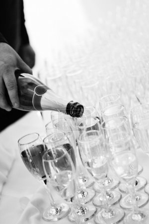 Waiter pours champagne