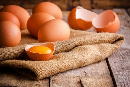 Photo for Fresh farm eggs on a wooden rustic background - Royalty Free Image