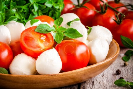 Mozzarella, organic cherry tomatoes and fresh basil closeup