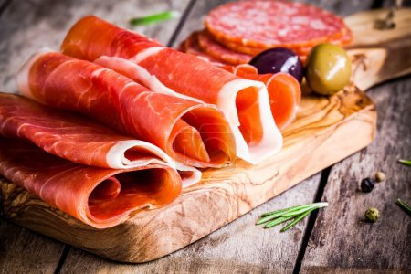 Photo for Thin slices of prosciutto with olives and salami on wooden cutting board - Royalty Free Image